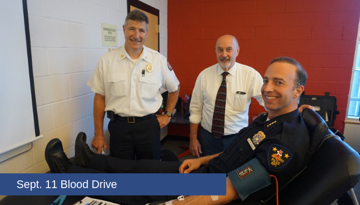 Fire Chief Eric McMahon, Mayor Patrick Madden, and Police Chief Brian Owens pose for a photo during Rensselaer Polytechnic Institute's annual September 11th blood drive. Chief Owens is seated, and Chief Owens and Mayor Madden are standing.