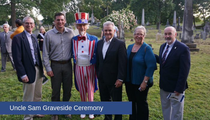 Peter Goebel, Director of Rensselaer County Veterans Services, Assemblyman Jake Ashby, Fred Polnish (Uncle Sam), Rensselaer County Executive Steve McLaughlin, Rensselaer County Historian Kathy Sheehan, and Mayor Patrick Madden pose for a photo in Oakwood Cemetery. Several gravestones are visible in the background.