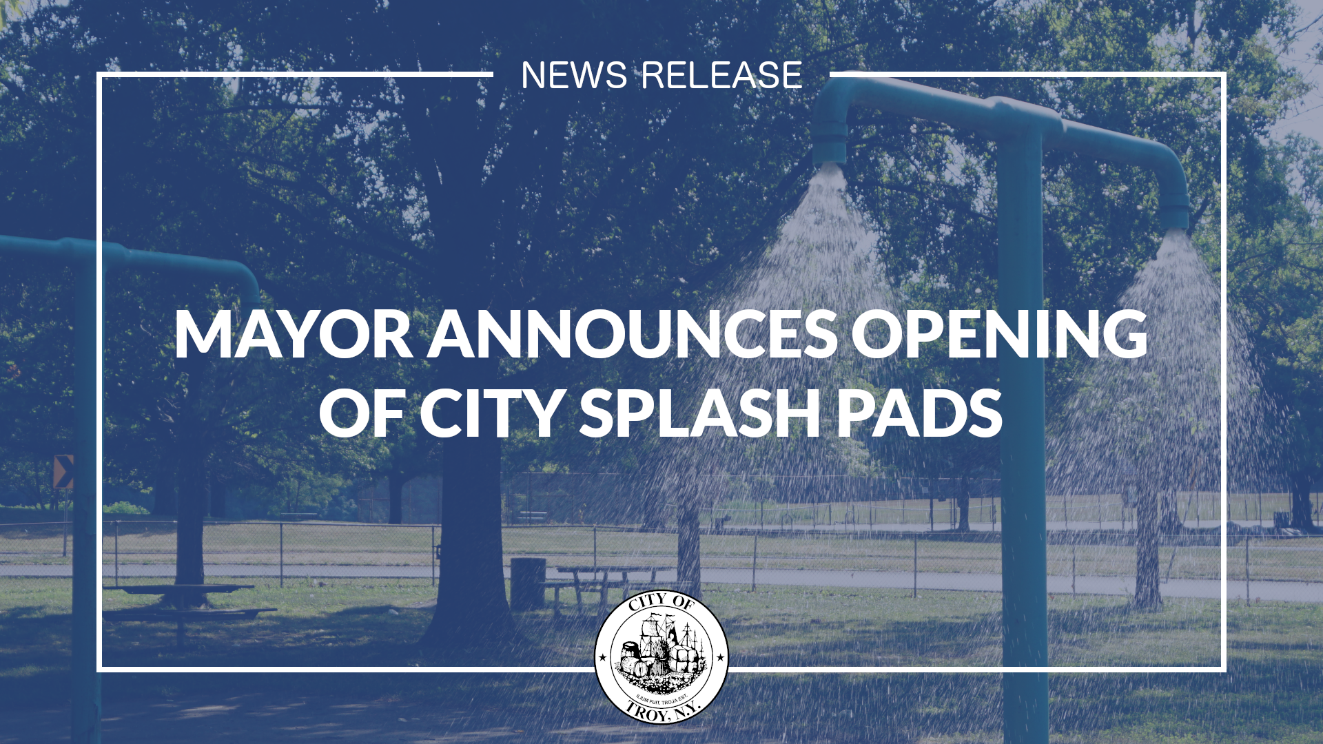 White text against dark blue background. Text reads Mayor Announces Opening of City Splash Pads. Image of a splash pad is visible in the background.