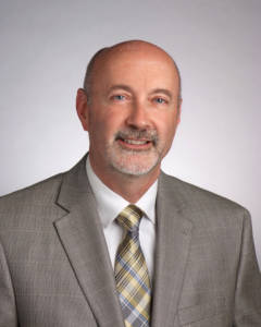 Promotional photo of Troy Mayor Patrick Madden. The mayor is visible from mid-chest upward.