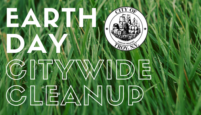 Zoomed in photo of green grass. The City logo is visible, with the text Earth Day Citywide Cleanup.