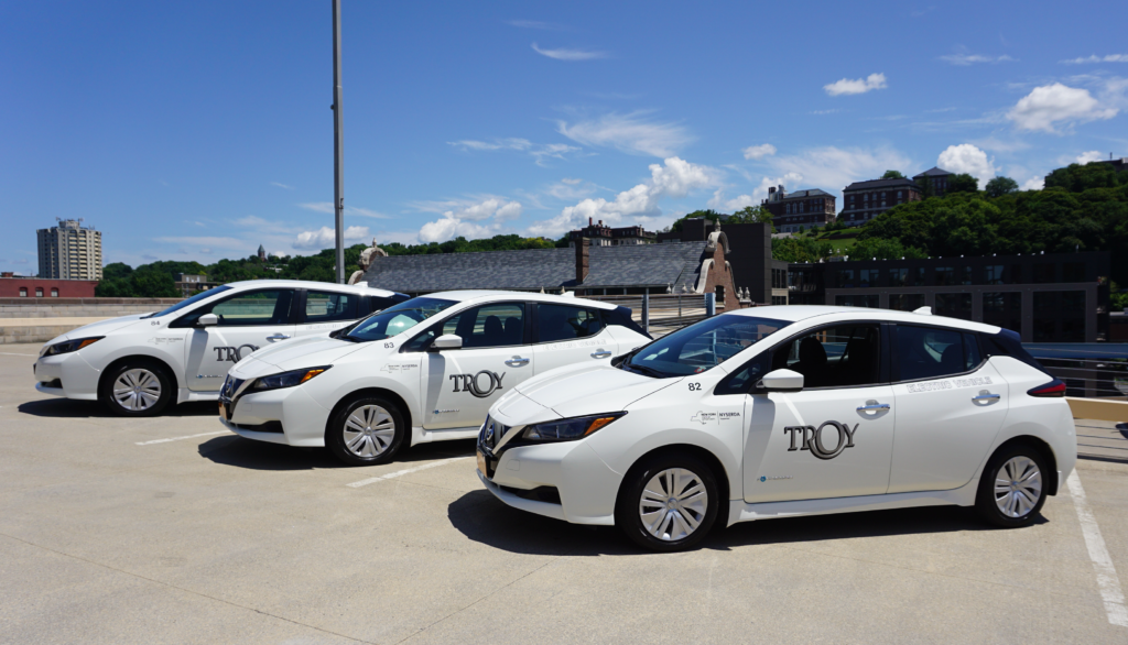 Three electric vehicles, painted white, are parked side by side. on a rooftop parking deck. The City of Troy municipal logo is visible on the drivers side door.
