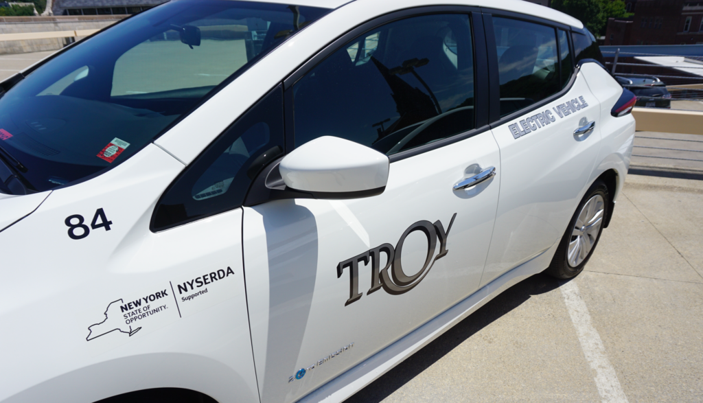 A close-up photo of the drivers side door of a white electric vehicle. he City of Troy municipal logo is visible on the drivers side door.