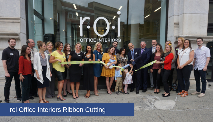 "A large group of people standing in front of a large window that says ""roi Office Interiors"" while holding a green ribbon. The ribbon has been cut and is beginning to fall to the ground."