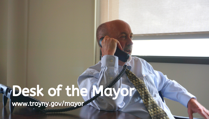 "Mayor Madden is seated while talking on a telephone. Text reads ""Desk of the Mayor"" and ""www.troyny.gov/mayor"""