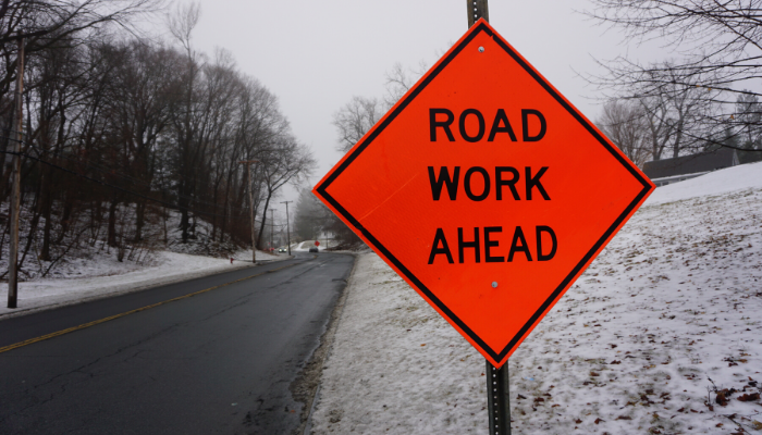 Orange road sign that reads Road Work Ahead. Snow-covered hillside and wet road, and cluster of trees are visible in the background.