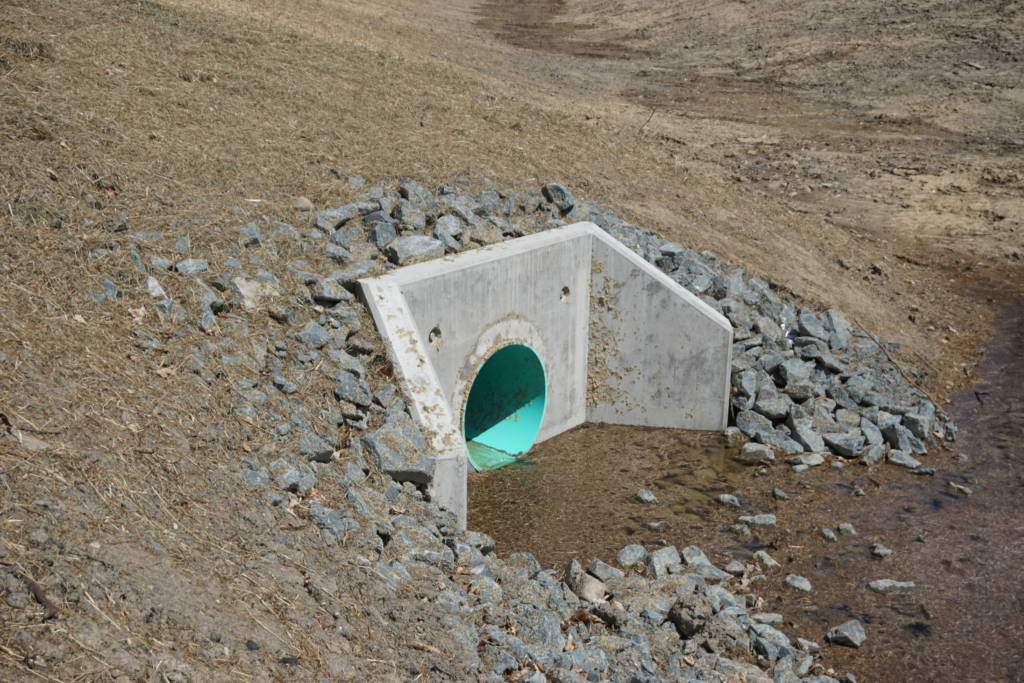 Water flows into a large concrete intake valve installed inside a hillside. The valve is surrounded by large stones.