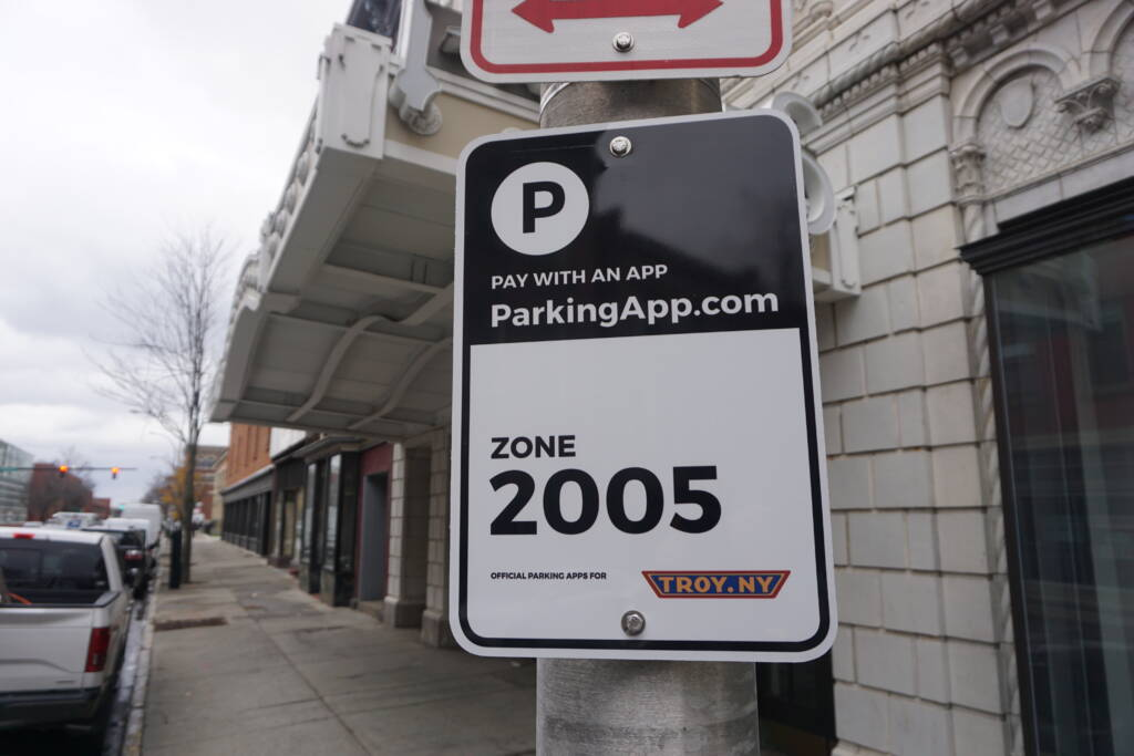 Metal street sign bolted to a metal pole in downtown Troy. The sign displays instructions on paying to park in downtown Troy.