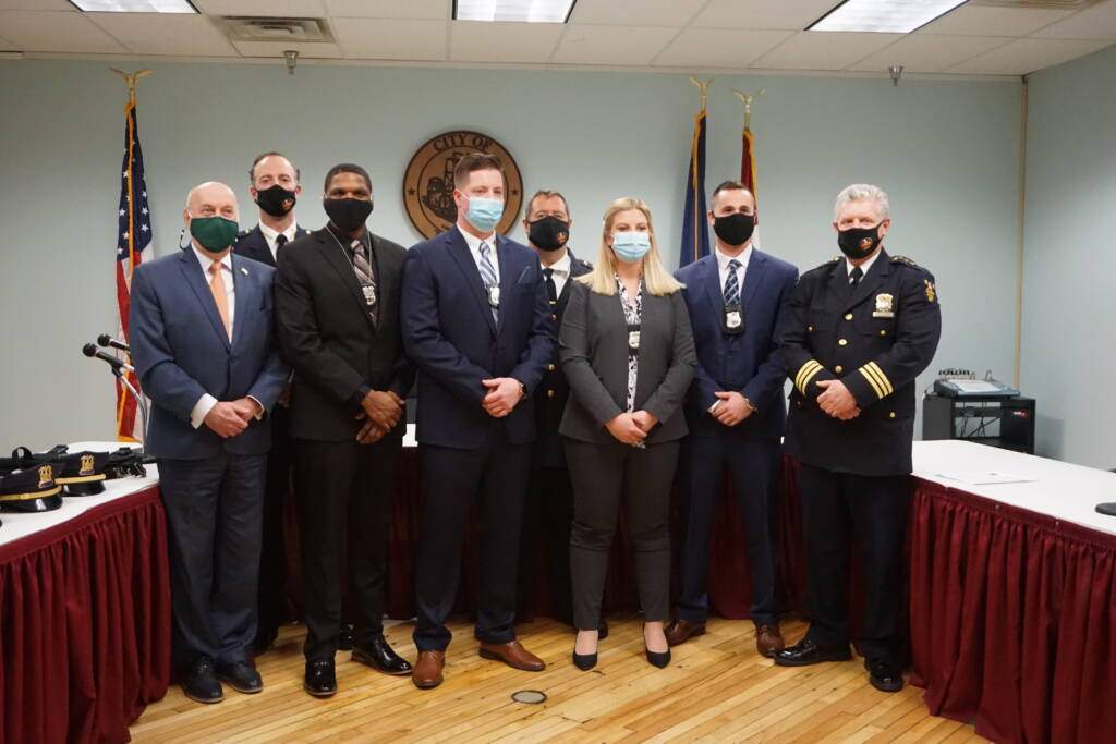Mayor Patrick Madden and Police Department leadership pose with four new police officers following a swearing in ceremony at City Hall. All are wearing masks due to COVID-19.