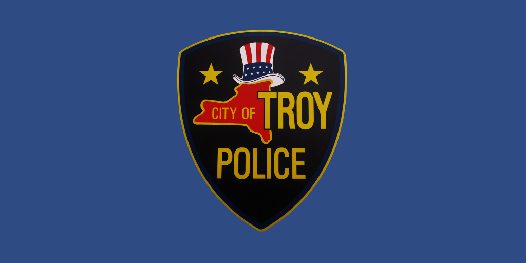 Seal of the Troy Police Department against a dark blue background