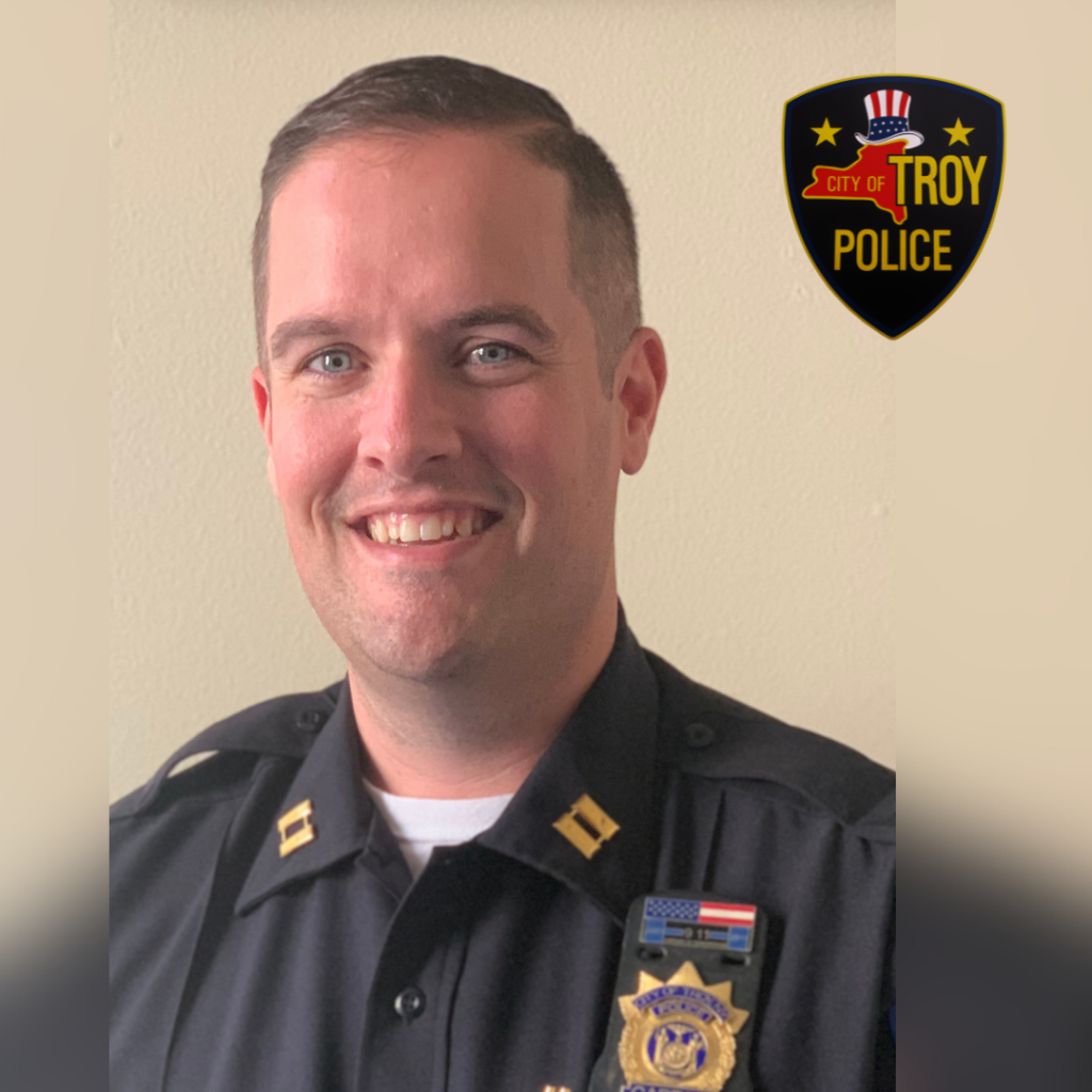 Photo of Captain Steven Barker in his police officer uniform. The Troy Police Department seal is visible in the top right corner.