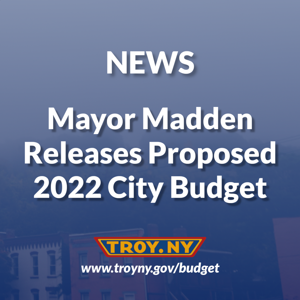 White text against a dark blue background that reads News: Mayor Madden Releases proposed 2022 City Budget. The TROY.NY logo and www.troyny.gov/budget is visible below the text. A photo of residential houses is partially visible in the background.